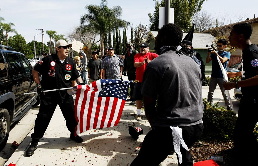 "A Ku Klux Klansman, left, uses an American flag to fend off angry counter protesters after members of the KKK tried to start a ""White Lives Matter"" rally at Pearson Park in Anaheim, Calif., on Saturday, Feb. 27, 2016. The event quickly escalated into violence and at least two people had to be treated at the scene for stab wounds. (Luis Sinco/Los Angeles Times via AP)"