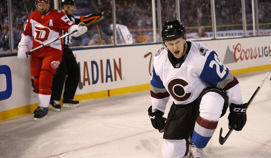 Colorado Avalanche center Nathan MacKinnon, front, reacts after scoring a goal as Detroit Red Wings defenseman Niklas Kronwall looks on in the first period of an NHL hockey game in Coors Field Saturday, Feb. 27, 2016, in Denver. (AP Photo/David Zalubowski)