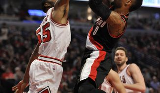 Portland Trail Blazers' Damian Lillard (0) goes up for a shot against Chicago Bulls' E'Twaun Moore (55) during the first half of an NBA basketball game Saturday, Feb. 27, 2016, in Chicago. (AP Photo/Paul Beaty)