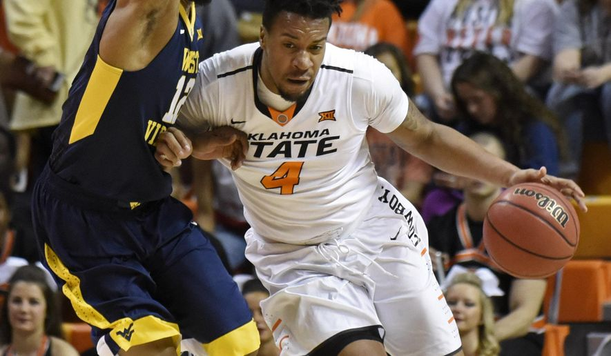 Oklahoma State guard Joe Burton, right, pushes off West Virginia guard Tarik Phillip in the first half of an NCAA college basketball game in Stillwater, Okla., Saturday, Feb. 27, 2016. (AP Photo/Brody Schmidt)