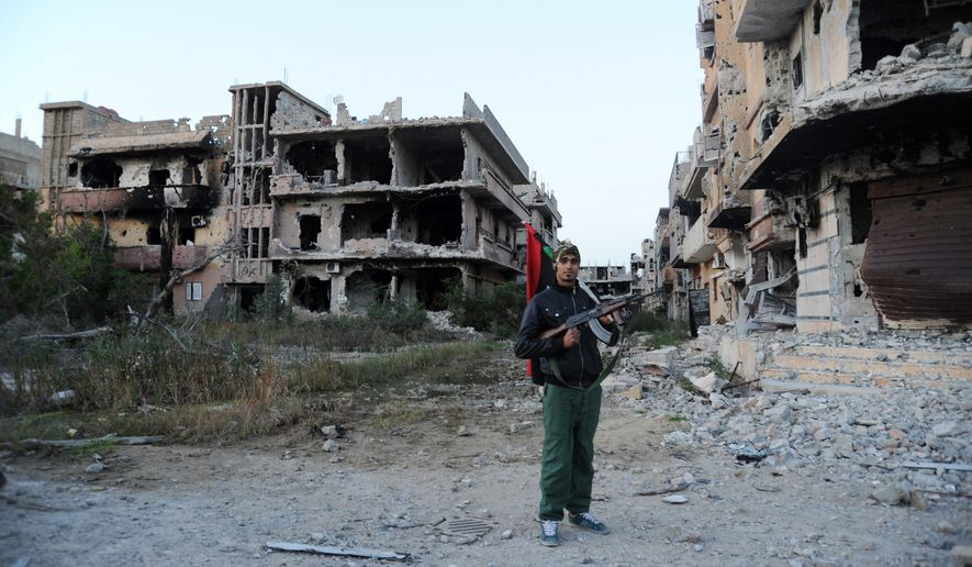 A civilian fighter in Benghazi has the Libyan flag in one hand and a weapon in the other. Army units, backed by civilian fighters, cleared a major part of the city of Islamic extremists last week. (Associated Press)