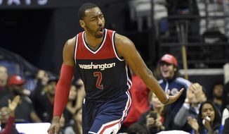 Washington Wizards guard John Wall (2) reacts during the first half of an NBA basketball game against the Cleveland Cavaliers, Sunday, Feb. 28, 2016, in Washington. (AP Photo/Nick Wass)