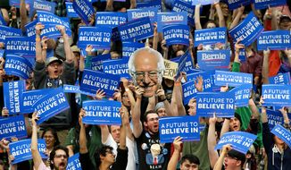 Students and supporters of Democratic presidential candidate Sen. Bernie Sanders, I-Vt., cheer and hold up signs, including one of Sanders, during a campaign rally at Colorado State University in Fort Collins, Colo., Sunday, Feb. 28, 2016. (AP Photo/Jacquelyn Martin)