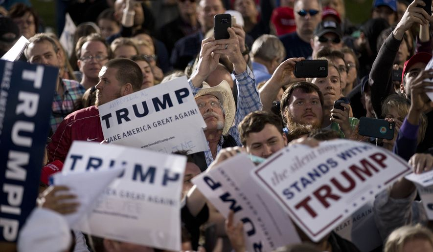 People attending a rally take photographs of Republican presidential candidate Donald Trump during a rally Sunday, Feb. 28, 2016, in Madison, Ala. (AP Photo/John Bazemore)