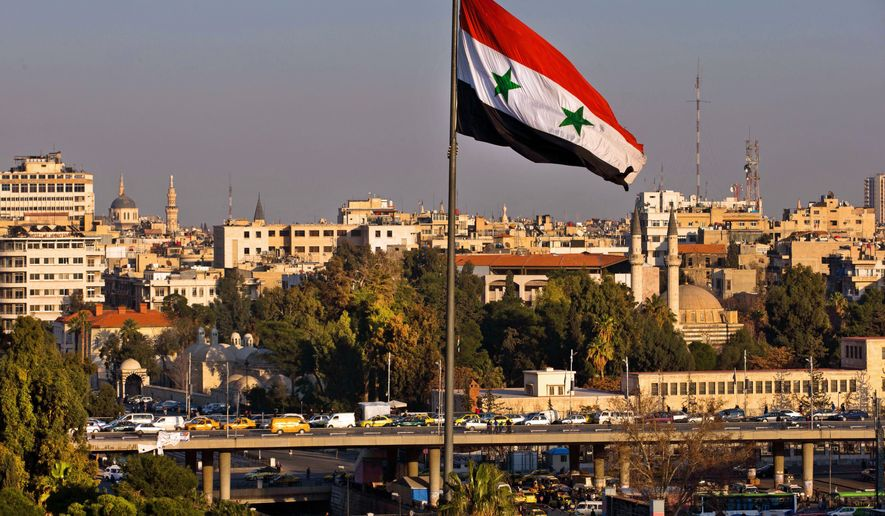 A Syrian national flag waves as vehicles move slowly on a bridge during rush hour, in Damascus, Syria, Sunday, Feb. 28, 2016. (AP Photo/Hassan Ammar)