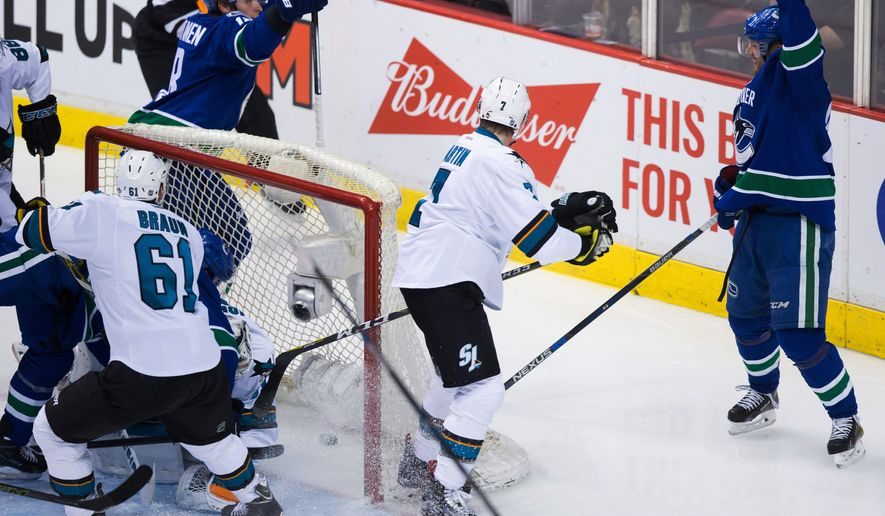 Vancouver Canucks' Jake Virtanen, top left, and Daniel Sedin, right, of Sweden, celebrate Sedin's goal as San Jose Sharks' Paul Martin, centre, and Justin Braun (61) look on during second period NHL hockey action in Vancouver on Sunday, Feb. 28, 2016. (Darryl Dyck/The Canadian Press via AP) MANDATORY CREDIT