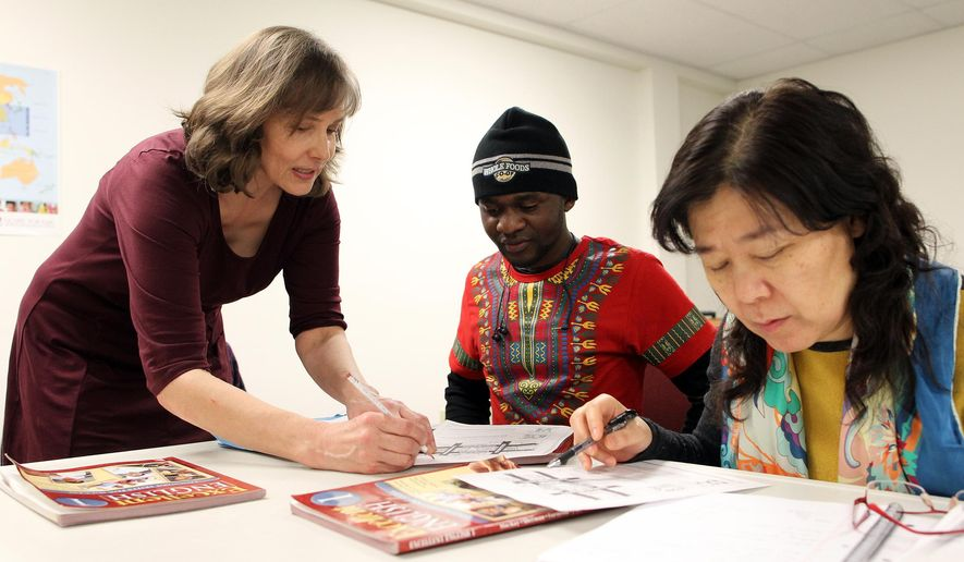 Susan Prepejchal works with 20-year-old Cedrick Buhendwa, a native of the Democratic Republic of the Congo, during an English class as part of the Friendship Community Project held at Good News Bible Church on Monday, Feb. 15, 2016 in Iowa City, Iowa. The Friendship Community Project started offering the volunteer-led classes in September to help adults from outside the U.S. learn English and navigate changes that come with moving to a new country, such as getting health insurance or addressing traffic tickets, said Susan Prepejchal, one of the project's teachers. (David Scrivner /Iowa City Press-Citizen via AP)  NO SALES; MANDATORY CREDIT