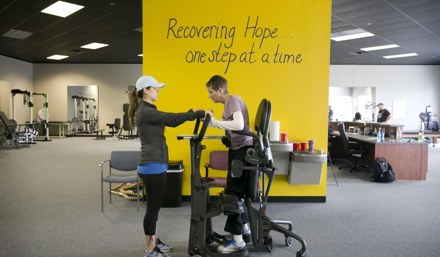 ADVANCE FOR THE WEEKEND OF FEB. 27 - In this Tuesday, Aug. 4, 2015 photo, Laurie Allen stands in a standing frame as she works with Nicole Thompson at Project Walk, a spinal cord injury recovery facility in Austin, Texas. (Jay Janner/Austin American-Statesman via AP) MANDATORY CREDIT