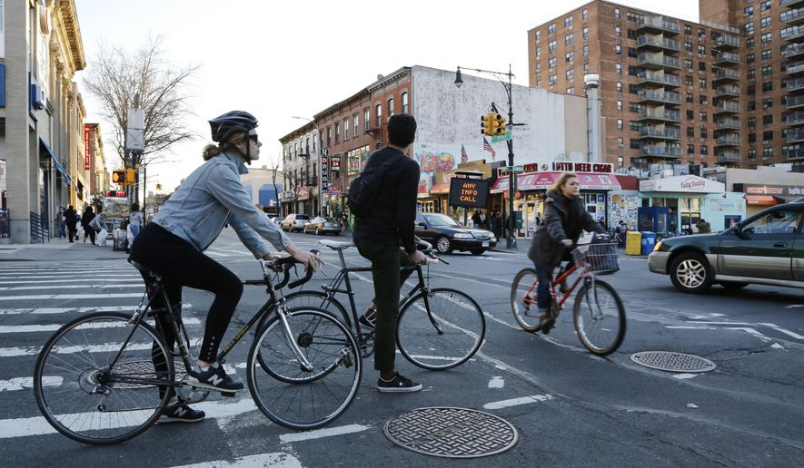 Bicyclists, left, wait for the traffic light to turn as another cyclist passes through the intersection of 9th St. and 5th Ave., Sunday, Feb. 28, 2016 in the Park Slope neighborhood of New York. Just before dawn Sunday police found a bicyclist lying unconscious in the intersection. The 41-year-old man died of severe trauma to the body. Police are looking for the motorist who drove away in a gold-colored sedan. (AP Photo/Mark Lennihan)