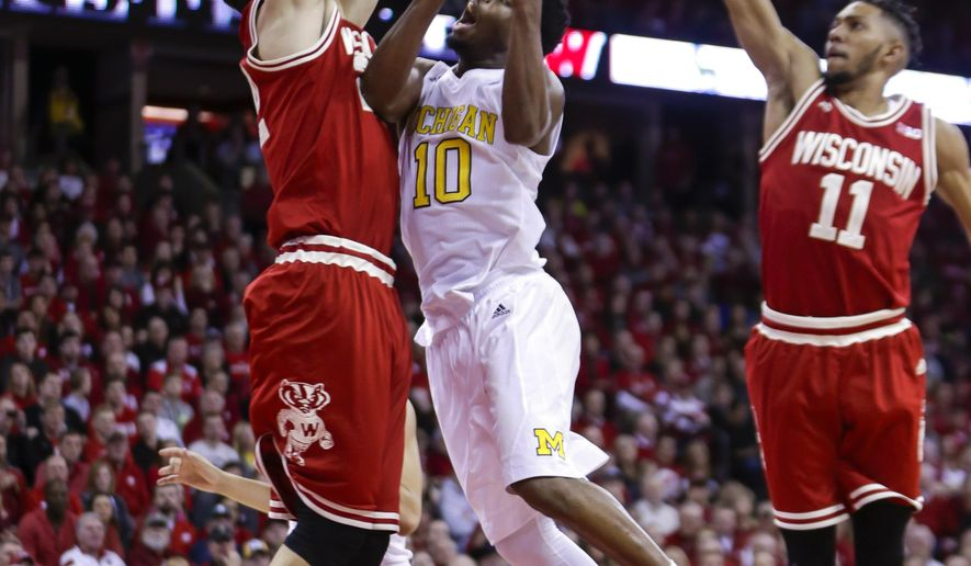 Michigan's Derrick Walton (10) shoots between Wisconsin's Ethan Happ, left, and Jordan Hill (11) during the first half of an NCAA college basketball game, Sunday, Feb. 28, 2016, in Madison, Wis. (AP Photo/Andy Manis)