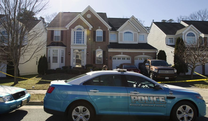 Police surround a home Sunday, Feb. 28, 2016, following a fatal shooting at the residence Saturday evening, in Woodbridge, Va. Ronald Williams Hamilton is being held without bond in the Prince William County Adult Detention Center on charges that include murder of a law enforcement officer. (AP Photo/Jose Luis Magana)