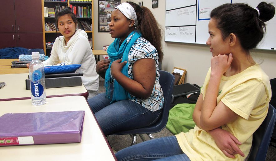 In this Jan. 26, 2016 photo, Nakafu Kahasha, center, describes her short story about her journey from Congo to Tanzania to Fargo, N.D., nearly six years ago, while Nepal natives Anju Tamang, left, and Anju Gurung listen during a break in their English language learners class at Fargo South High School. The three students are among others in the class who wrote stories about their resettlement for a self-published book that has been popular in the school. (AP Photo/Dave Kolpack)