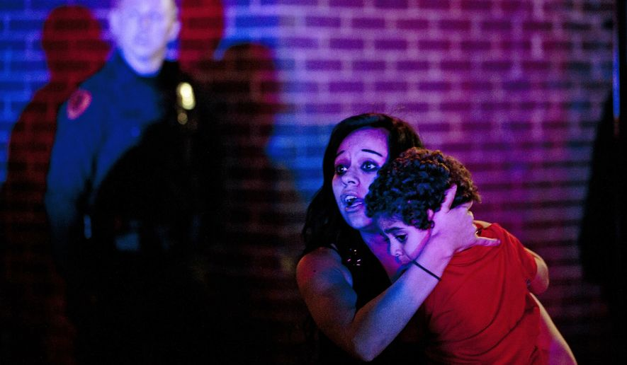 A woman holds a young boy as a crowd of people clash with police following an officer-involved shooting at 200 South Rio Grande Street in Salt Lake City, Saturday, Feb. 27, 2016. Unrest broke out in a Salt Lake City neighborhood on Saturday night after what appears to be a shooting involving a police officer, the Salt Lake Tribune reported. (Lennie Mahler/The Salt Lake Tribune via AP)