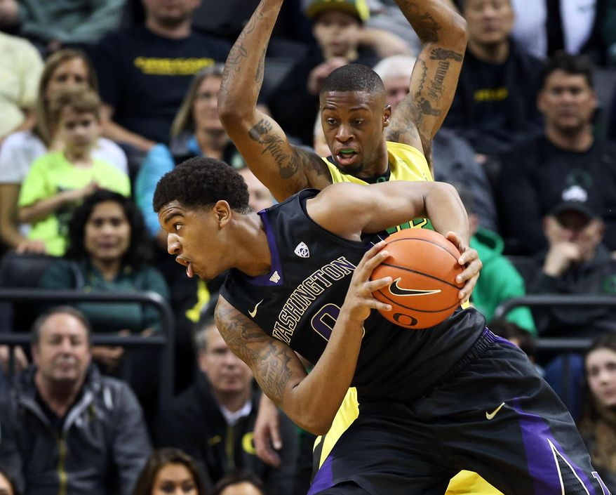 Washington's Marquese Chriss, foreground, battles Oregon's Elgin Cook for position under the basket during the first half of an NCAA college basketball game, Sunday, Feb. 28, 2016, in Eugene, Ore. (AP Photo/Chris Pietsch)
