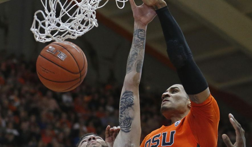 Oregon State's Gary Payton II, right, dunks over Washington State's Derrien King in the first half of an NCAA college basketball game in Corvallis, Ore., on Sunday, Feb. 28, 2016. (AP Photo/Timothy J. Gonzalez)