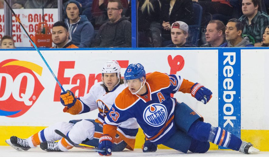 New York Islanders' Matt Martin (17) slides into the boards with Edmonton Oilers' Matt Hendricks (23) during second period NHL hockey action in Edmonton on Sunday, Feb. 28, 2016. (Amber Bracken/The Canadian Press via AP) MANDATORY CREDIT