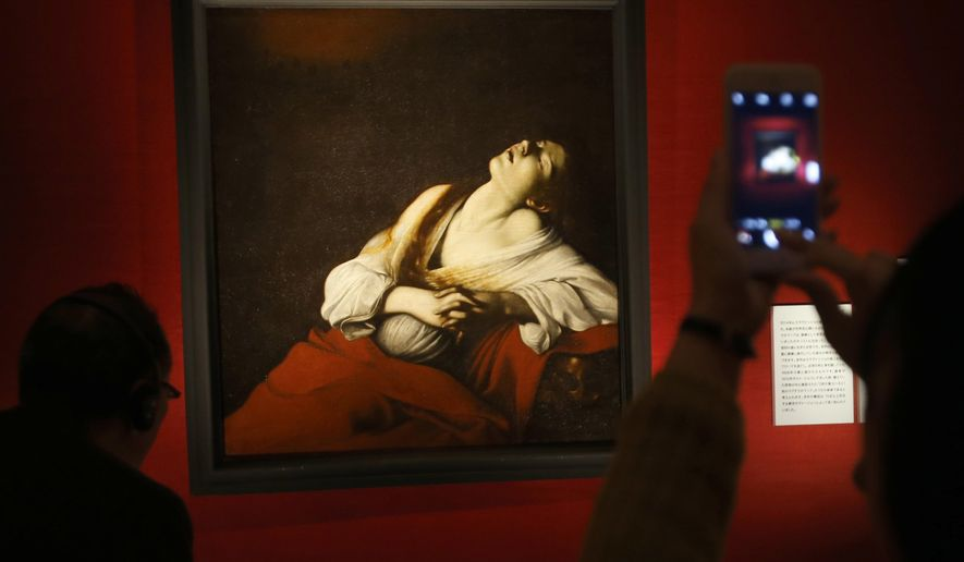 "People look at ""Maria Magdalene in Ecstasy"" by Italian maestro Caravaggio during the media preview prior to the opening ceremony of the ""Caravaggio and His Time: Friends Rivals and Enemies"" exhibition in Tokyo, Monday, Feb. 29, 2016. The painting, which was discovered in 2014 by a leading Caravaggio scholar among his family heirlooms after being lost for more than 400 years, will be shown to the public for the first time in the world at the exhibition starting Tuesday, March 1 along with his 10 other paintings at the National Museum of Western Art in Tokyo. (AP Photo/Shizuo Kambayashi)"