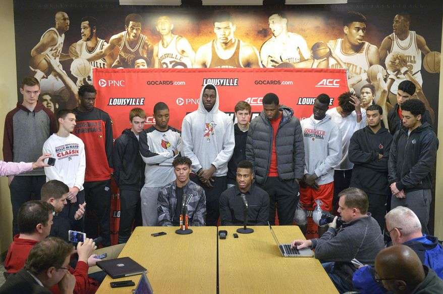 FILE - In this Feb. 5, 2016, file photo, surrounded by teammates, Louisville graduate students Damion Lee, seated left, and Trey Lewis meet with reporters during a press conference, in Louisville Ky. Louisville's decision to sit out the postseason because of recruiting violations dashed the dreams of Trey Lewis and Damion Lee to play in the NCAA Tournament. But they enter Tuesday night's, March 1, 2016, home finale consoled by helping the Cardinals achieve success nobody envisioned when they transferred there.  (AP Photo/Timothy D. Easley, File)