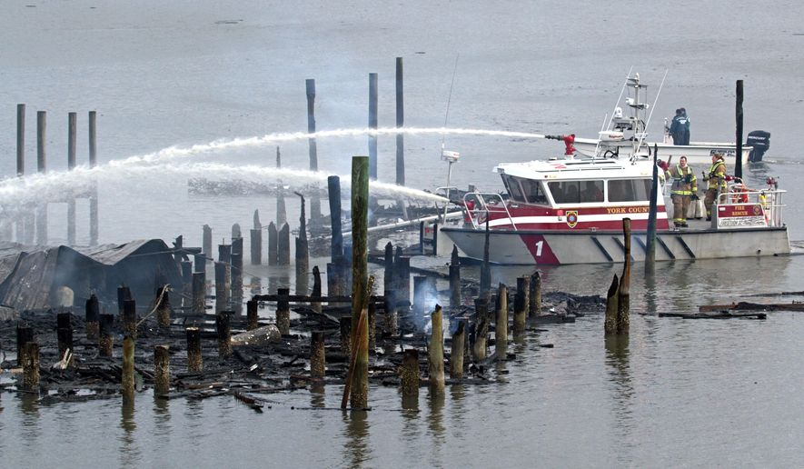 A fireboat crew pumps water onto a pier at the Dozier Yachting Center Marina, after a fire damaged about 50 boats early Monday, Feb. 29, 2016, in Urbanna, Va. (Joe Fudge/The Daily Press via AP) MANDATORY CREDIT