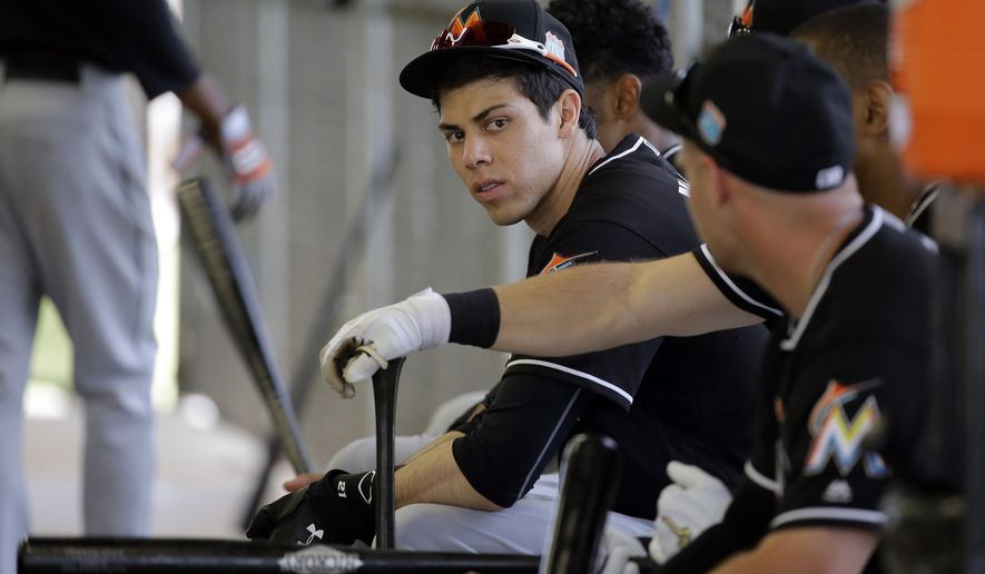Miami Marlins' Christian Yelich waits with teammates to workout in a batting cage during spring training baseball practice Monday, Feb. 29, 2016, in Jupiter, Fla. (AP Photo/Jeff Roberson)