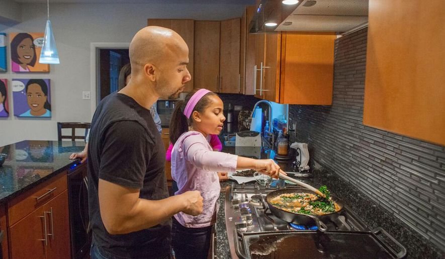 In this Jan. 23, 2016, photo, Taryn Robinson cooks white turkey chili, a meal kit dish from Blue Apron, as her father, Keith Robinson, watches over her shoulder in Evanston, Ill. Meal kits are fairly new in the U.S., first appearing in the country about four years after first gaining popularity in Europe. The industry is growing quickly and competition is heating up as more players enter the space and fight to gain customers. (AP Photo/Teresa Crawford)