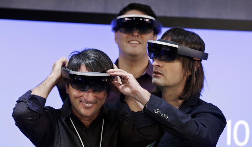 FILE - In this Jan. 21, 2015, file photo, Microsoft's Joe Belfiore, left, smiles as he tries on a HoloLens device with colleagues Alex Kipman, right, and Terry Myerson following an event demonstrating new features of Windows 10 at the company's headquarters in Redmond, Wash. Microsoft said it will start shipping a developer version of its augmented reality device, HoloLens, for $3,000, by the end of March 2016. (AP Photo/Elaine Thompson, File)