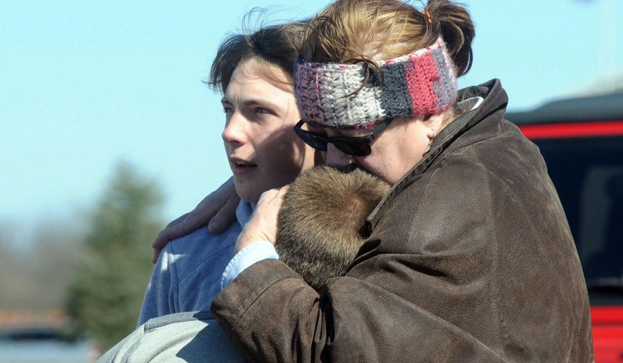 A child is comforted Monday, Feb. 29, 2016, near Middletown, Ohio after a school shooting at Madison Local Schools.  An Ohio sheriff says a 14-year-old suspect in a school shooting that wounded four classmates, including two who were shot, is in a juvenile lock-up and facing several charges. Butler County Sheriff Richard Jones says the boy has been charged with two counts of attempted murder, two counts of felonious assault, inducing panic and making terrorist threats.  (Marshall Gorby/Dayton Daily News via AP)