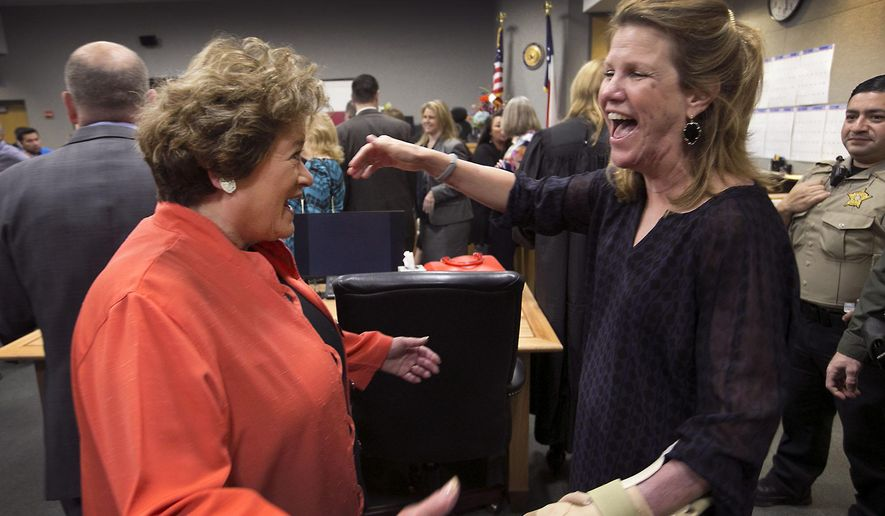 Travis County District Judge Julie Kocurek, right, was welcomed back to the bench by District Attorney Rosemary Lehmberg, left, Monday, Feb. 29, 2016, in Austin, Texas, after spending weeks recovering from an assassination attempt in November of last year. She said she felt reborn and though she is still undergoing physical therapy for her wounds will spend only half days on the bench for now. (Ralph Barrera/Austin American-Statesman via AP)