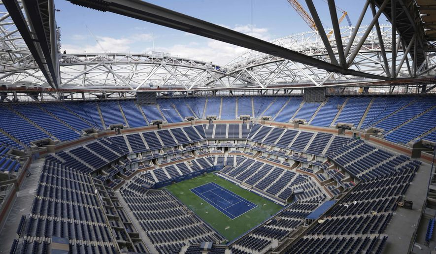 The framework of a retractable roof is seen over Arthur Ashe Stadium at the USTA Billie Jean King National Tennis Center in New York, Monday, Feb. 29, 2016. U.S. Open organizers plan to try to avoid closing the new roof over Arthur Ashe Stadium as much as possible, even if that means wet courts making for a longer delay. (AP Photo/Seth Wenig)