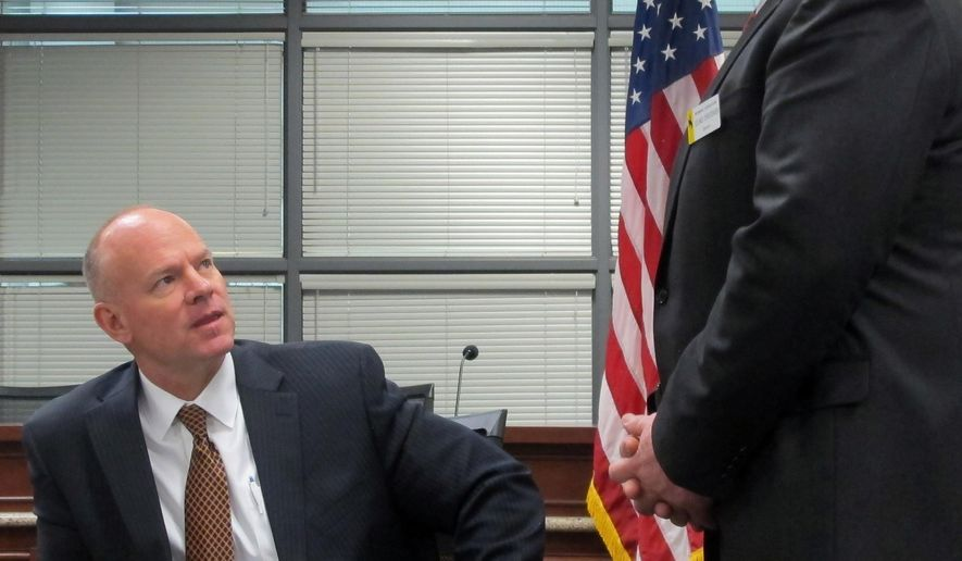 Wyoming Gov. Matt Mead, seated, talks to Sen. Leland Christensen, R-Alta, at a bill-signing ceremony in Cheyenne, Wyo., Monday, Feb. 29, 2016. Mead signed a bill sponsored by the Legislature's Joint Judiciary Committee that establishes a legal process for forfeiting assets that law enforcement believes were involved in the illegal drug trade. (AP Photo/Ben Neary)