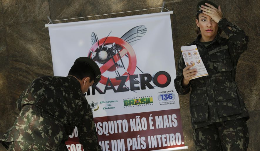 "FILE - In this Saturday, Feb. 13, 2016 file photo, army soldiers set up a sign that reads in Portuguese ""A mosquito is not stronger than an entire country"" at the Central station in Rio de Janeiro, Brazil, as troops across Brazil try to tackle the Zika virus. Scientists may have the first evidence that Zika causes temporary paralysis, according to a new study of patients who developed the rare condition during an outbreak of the virus in Tahiti two years ago. The research was published online Monday, Feb. 29 in the journal, Lancet.  (AP Photo/Silvia Izquierdo, file)"