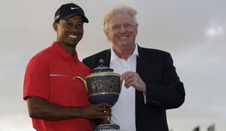Tiger Woods stands with Donald Trump as he holds the Gene Serazen Cup for winning the Cadillac Championship golf tournament Sunday, March 10, 2013, in Doral, Fla. Woods won with a score 19-under-par 269. (AP Photo/Wilfredo Lee)