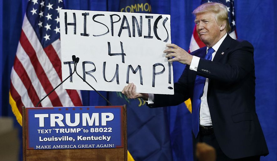 Republican presidential candidate Donald Trump holds up a sign he borrowed from a spectator during a rally Tuesday, March 1, 2016, in Louisville, Ky. (AP Photo/John Bazemore)