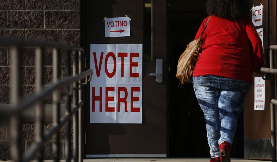 A voter walks in to cast her ballot during Alabama's primary at a polling site, Tuesday, March 1, 2016, in Birmingham, Ala.  Voters from Vermont to Colorado, Alaska to American Samoa and a host of states in between were heading to polling places and caucus sites on the busiest day of the 2016 primaries. (AP Photo/Brynn Anderson)