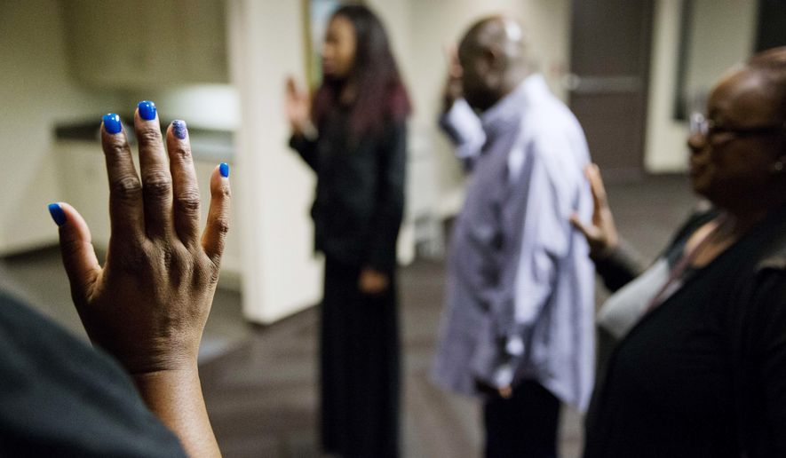 Tameika Ogburn, a polling site assistant manager, raises her hand during a swearing-in with fellow workers at a polling site before it opens to voters casting ballots in Georgia's primary election Tuesday, March 1, 2016, in Atlanta. (AP Photo/David Goldman)
