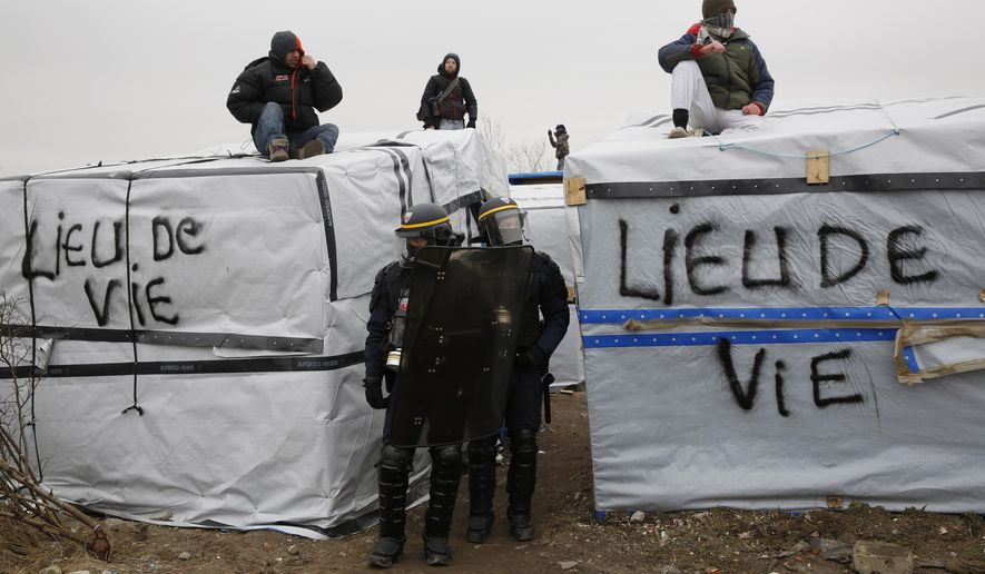 Migrants and activists stand on the roofs of dwellings in an attempt to prevent them from being dismantled, as police patrol, in a makeshift camp near Calais, France, Tuesday March 1, 2016. The slow tear-down of the encampment in Calais continued Tuesday, angering migrants who live there in squalid conditions in hopes of reaching a better life in Britain. (AP Photo/Jerome Delay)