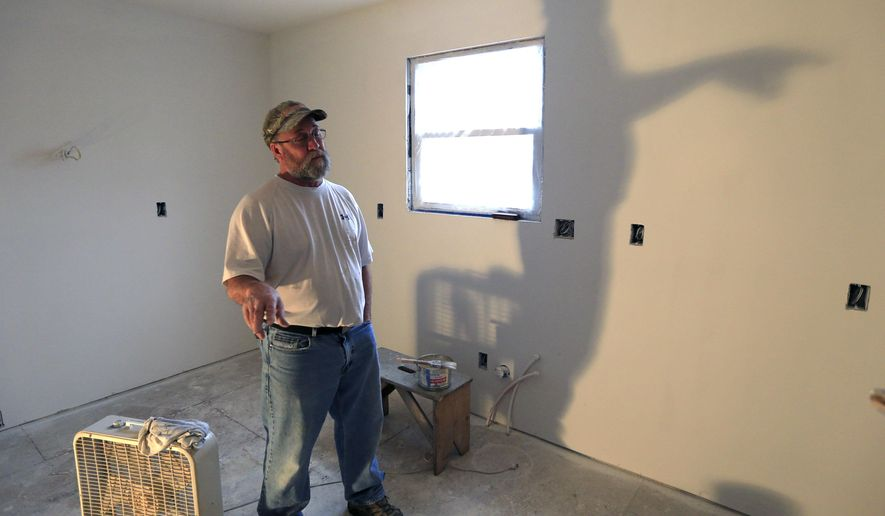 Danny Jones, construction manager for Habitat for Humanity, takes a break from painting at a newly built home in Topeka, Kan., Thursday, Feb. 25, 2016. A Kansas Senate bill would allow nonprofit organizations like Habitat for Humanity to gain control of abandoned houses and rehabilitate them before they are beyond repair. Critics, however, worry the measure would unfairly target disadvantaged people who can't afford to maintain their homes. (AP Photo/Orlin Wagner)