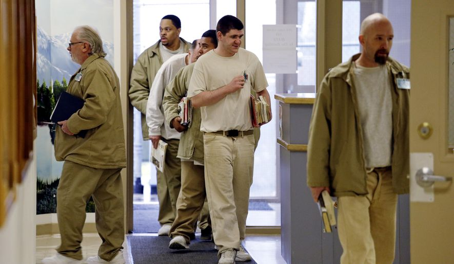 Inmates carry books as they head to classes at the Monroe Correctional Complex in Monroe, Wash., on Jan. 28, 2016. College education in American prisons is starting to grow again, more than two decades since federal government dollars were prohibited from being used for college programs behind bars. The shift comes as everyone from President Barack Obama to state policymakers are looking for ways to get better results from the $80 billion the U.S. spends annually on incarceration. (Associated Press) **FILE**