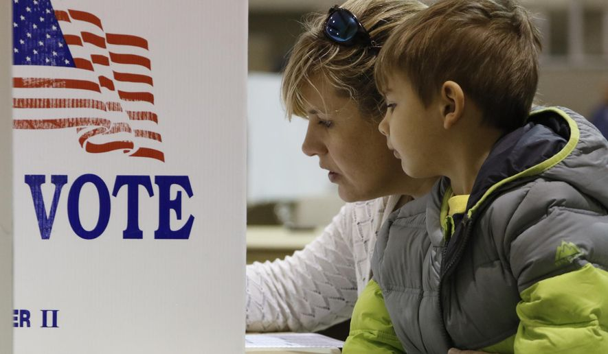 Brooke Stanfill votes with her 4-year-old son Charlie at Concord Baptist Church during the primary election in East Brainerd, Tenn., on Tuesday, March 1, 2016. Voters from Vermont to Colorado, Alaska to American Samoa and a host of states in between were heading to polling places and caucus sites on the busiest day of the 2016 primaries. (Dan Henry/Chattanooga Times Free Press via AP) THE DAILY CITIZEN OUT; NOOGA.COM OUT; CLEVELAND DAILY BANNER OUT; LOCAL INTERNET OUT; MANDATORY CREDIT