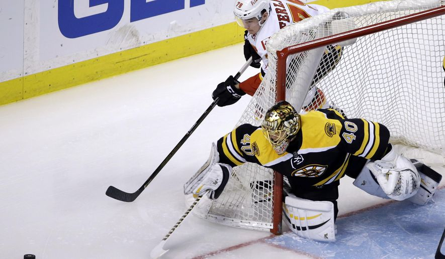 Boston Bruins goalie Tuukka Rask (40) reaches for the puck to defend against Calgary Flames left wing Micheal Ferland (79) in the first period of an NHL hockey game, Tuesday, March 1, 2016, in Boston. (AP Photo/Elise Amendola)