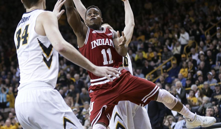 Indiana guard Yogi Ferrell drives to the basket over Iowa center Adam Woodbury, left, during the first half of an NCAA college basketball game Tuesday, March 1, 2016, in Iowa City, Iowa. (AP Photo/Charlie Neibergall)