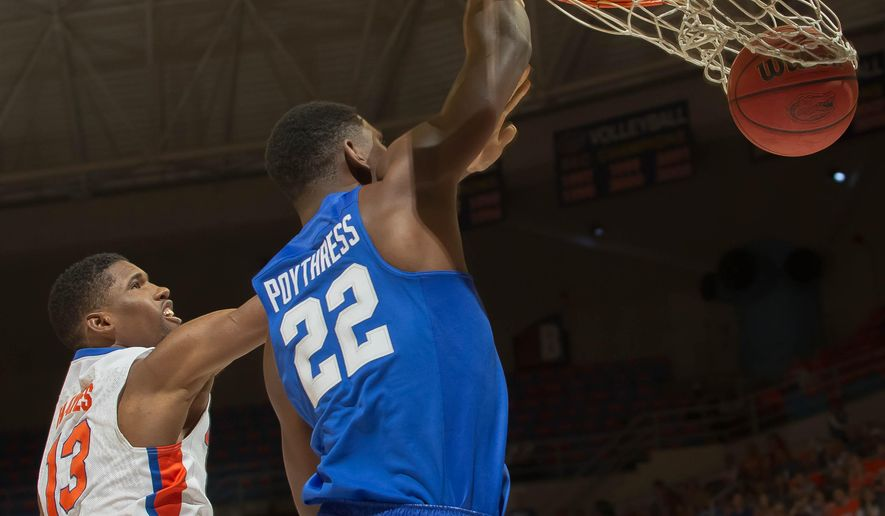 Kentucky forward Alex Poythress (22) dunks the ball over the defense of Florida forward Kevarrius Hayes (13) during the first half of an NCAA college basketball game in Gainesville, Fla., on Tuesday, March 1, 2016. (AP Photo/Ronald Irby)