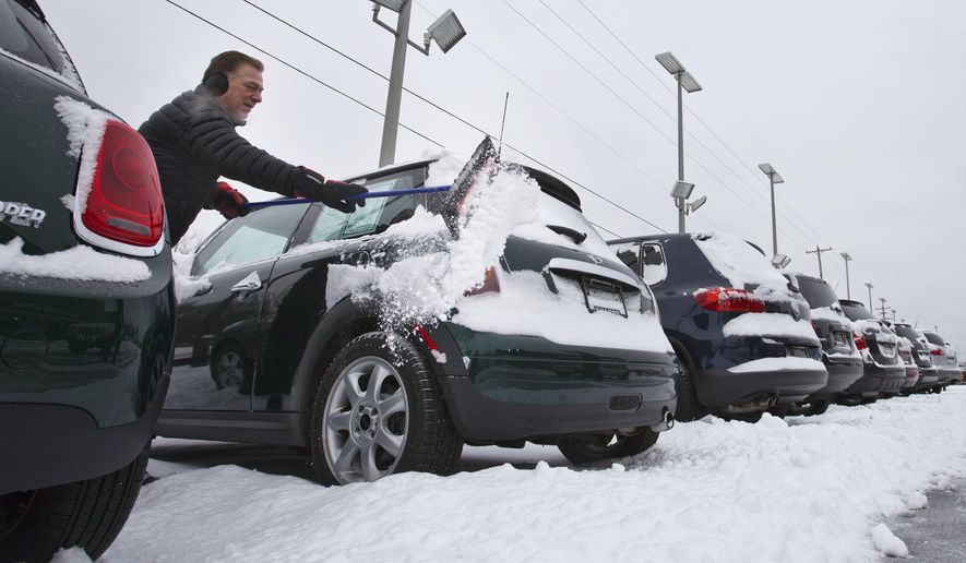 Mike Kelly cleans snow off cars at The Sharpe Collection, in Grand Rapids, Mich., Tuesday, March 1, 2016.  (Cory Morse/The Grand Rapids Press via AP)
