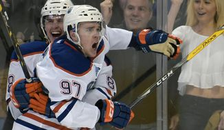 Edmonton Oilers defenseman Brandon Davidson, left, celebrates with center Connor McDavid (97) after McDavid scored in overtime of an NHL hockey game against the Buffalo Sabres, Tuesday, March 1, 2016, in Buffalo, N.Y.  Edmonton won 2-1. (AP Photo/Gary Wiepert)