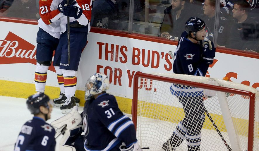 Florida Panthers' Vincent Trocheck (21) and Reilly Smith (18) celebrate after Smith scored on Winnipeg Jets goaltender Ondrej Pavelec (31) during the first period of an NHL hockey game Tuesday, March 1, 2016, in Winnipeg, Manitoba. (Trevor Hagan/The Canadian Press via AP)