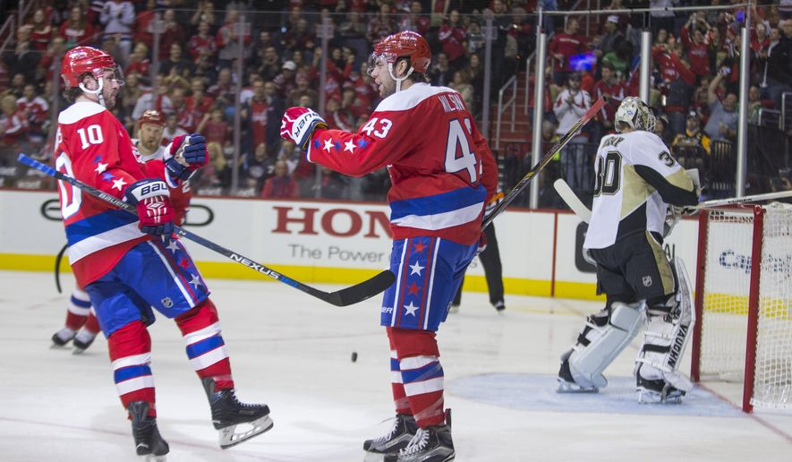 Washington Capitals right wing Tom Wilson, center, congratulates center Mike Richards, left, after he scored a goal past Pittsburgh Penguins goalie Matt Murray during the second period of an NHL hockey game Tuesday, March 1, 2016, in Washington. (AP Photo/Evan Vucci)