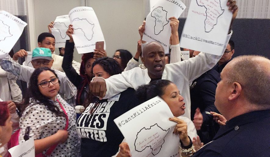 Protesters interrupt a meeting of the Los Angeles Police Commission on Tuesday, March 1, 2016, to decry the shooting of a homeless black man by the LAPD exactly one year ago. The protest came the same day the police department released a report showing that when LAPD officers fire at suspects, their targets are disproportionately black and mentally ill. (AP Photo/Amanda Lee Myers)