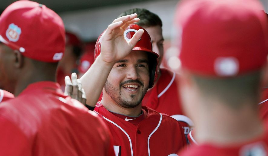 Cincinnati Reds' Eugenio Suarez smiles has he gets high-fives from teammates in the dugout after he scored a run against the Cleveland Indians during the first inning of a spring baseball game Tuesday, March 1, 2016, in Goodyear, Ariz. (AP Photo/Ross D. Franklin)