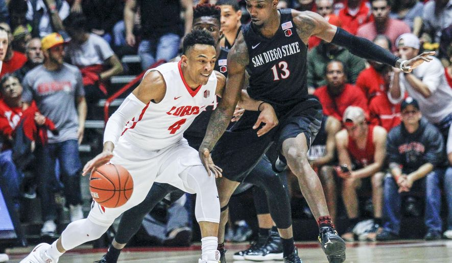 New Mexico's Elijah Brown (4) drives to the hoop guarded by San Diego State's Winston Shepard (13) during the first half of an NCAA basketball game, Tuesday, March 1, 2016, in Albuquerque, N.M. (AP Photo/Juan Labreche)