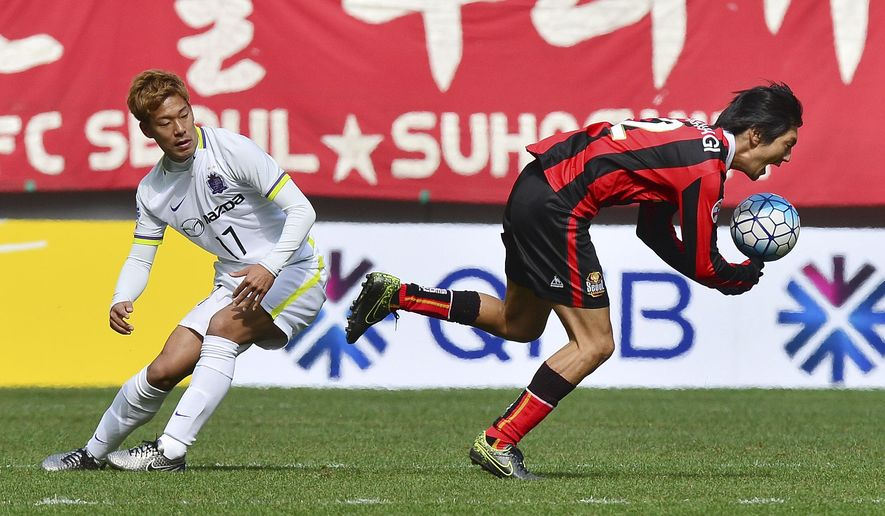 South Korea's FC Seoul midfielder Yojiro Takahagi, right, fights for the ball against Japan's Sanfrecce Hiroshima midfielder Gakuto Notsuda during a soccer match of the AFC Champions League at the World Cup Stadium in Seoul, South Korea, Tuesday, March 1, 2016. (Go Sung-min/Newsis via AP) KOREA OUT